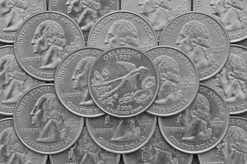Oklahoma State and coins of USA. Pile of the US quarter coins with George Washington and on the top a quarter of Oklahoma State royalty free stock images