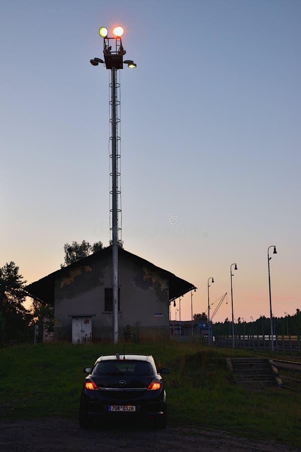 Okna, Ceska Lipa区,捷克共和国- 2018年7月14日:停放的汽车欧宝雅特H,大厦和高灯在小火车站 库存照片