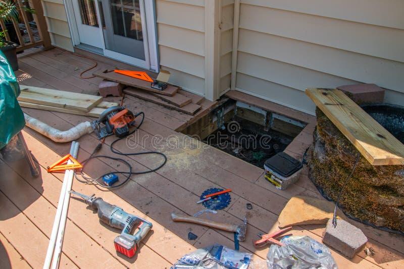 Okno cięcie w brązu drewnianego pokład po to, aby naprawiać drenażowego problem pod pokładem Tam są różnorodni władz narzędzia na obrazy royalty free