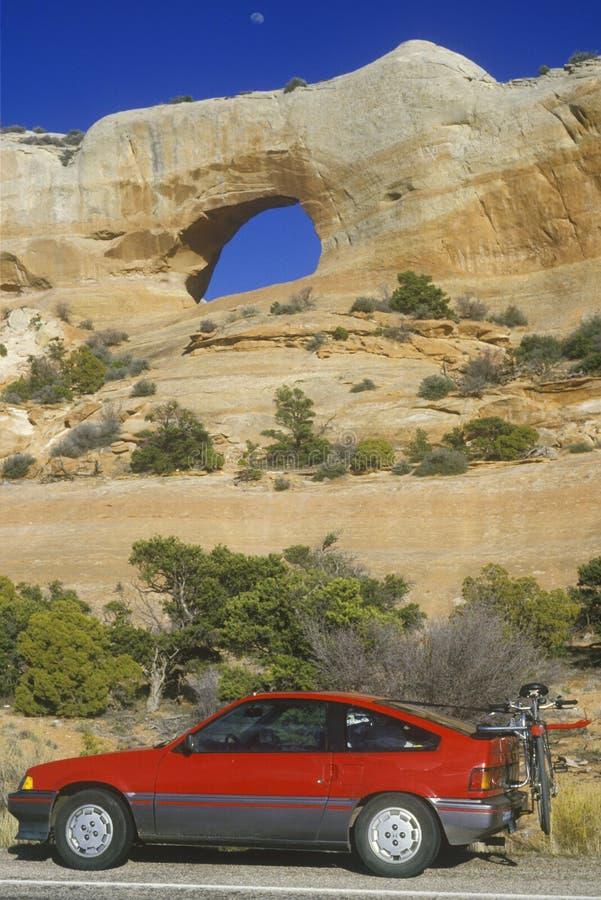Okno skały łuk w południowym UT z czerwonym samochodem w przedpolu obrazy royalty free