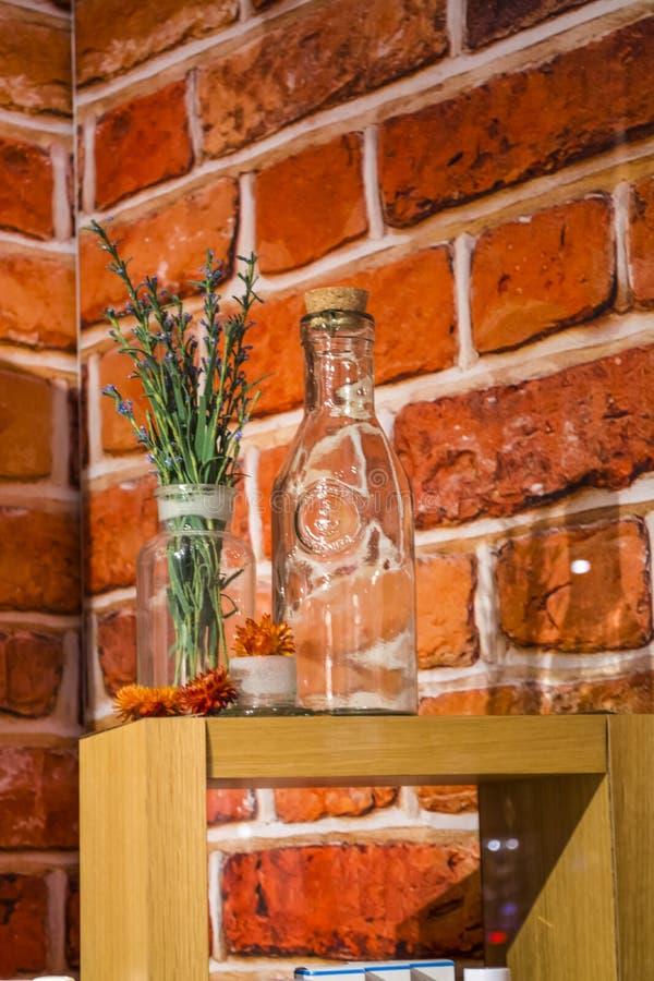 Okno w sklepie kosmetyki na tle czerwone cegły Na drewnianego poparcia szklanych butelkach, fiołków ziele i kwiaty i obrazy stock
