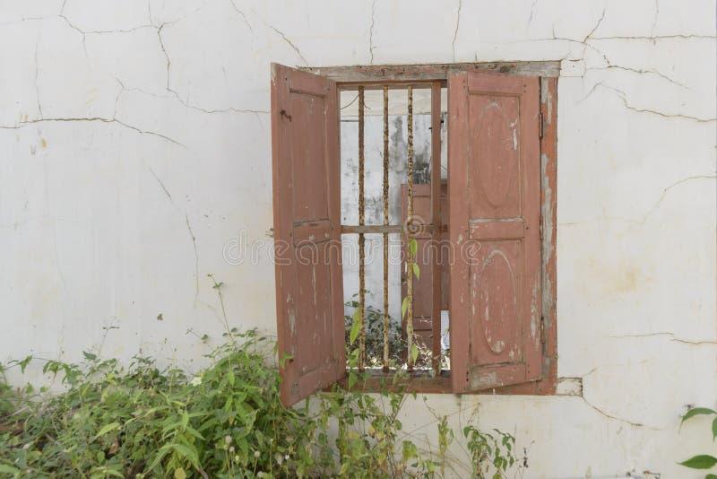 Okno w starym, zaniechanym domu z drewnianymi żaluzjami i ośniedziałym grillem, obrazy stock