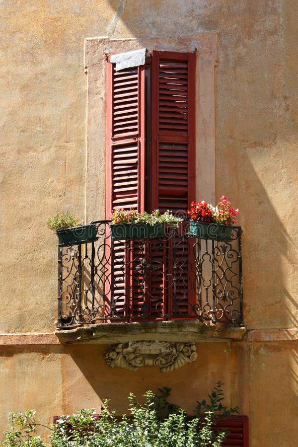 Okno z drewnianymi storami i balkonem z kwiatami, włoszczyzna obraz royalty free
