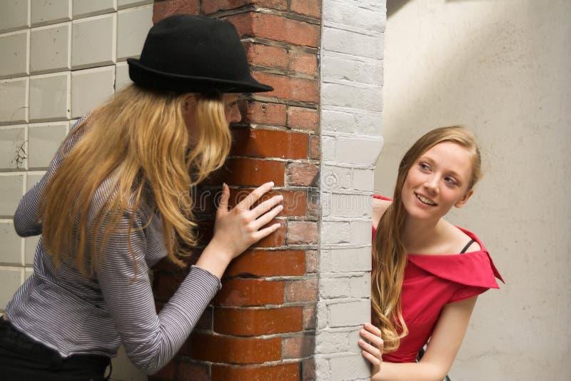 około dwóch dziewczyn zerkania ściany obraz royalty free