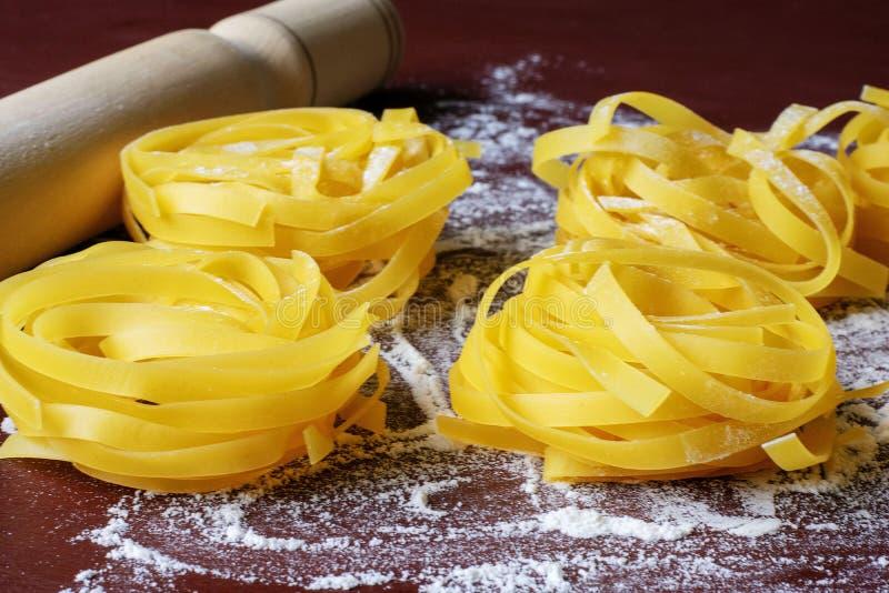 Okokt pasta p? en m?rk bakgrund som strilas med mj?l, n?ra kavlen royaltyfri bild