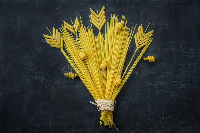 Okokt spagetti Penne Pasta Arranged i sammansättning av veteörabuketten på svart stenbakgrund Menyaffischmall arkivfoton