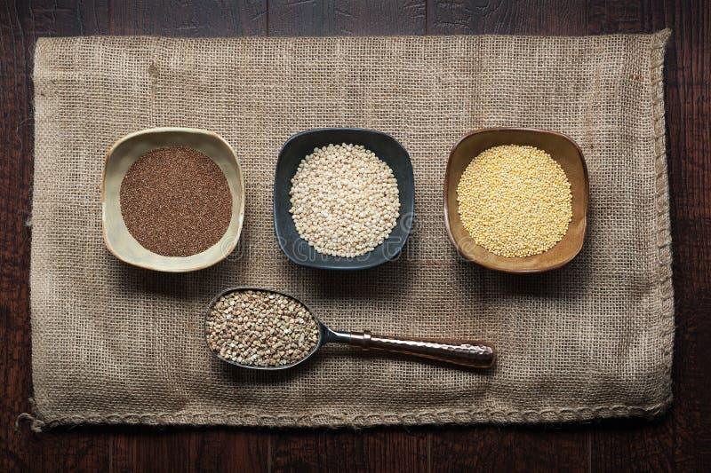 Okokta forntida korn av teff, duren, hirs och bovete kärnar ur in formen royaltyfri bild