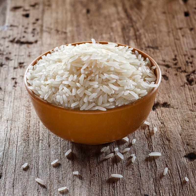 Okokta torra ris i brun bunke royaltyfria foton