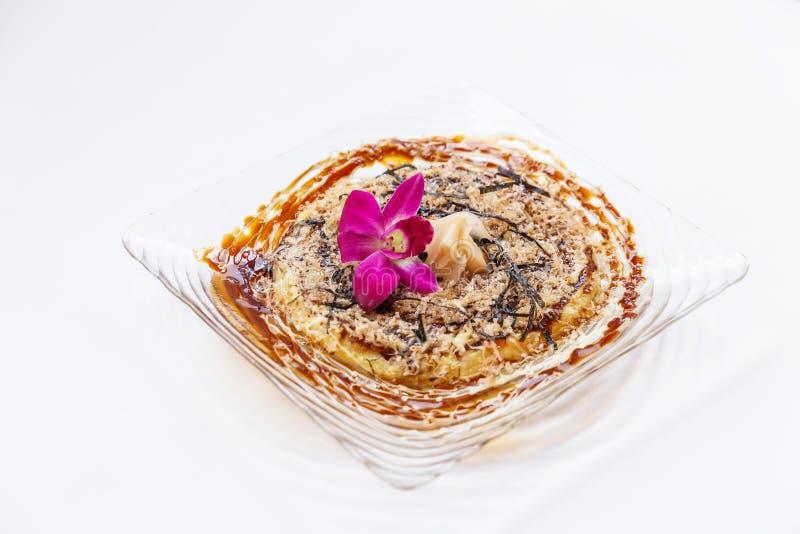 Okonomiyaki es una crepe sabrosa japonesa que contiene una variedad de ingredientes imagenes de archivo
