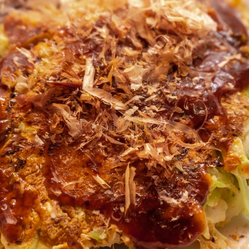 Okonomiyaki - Japanese pancake with bacon and cabbage, a spicy sauce and sprinkled with Bonito royalty free stock image