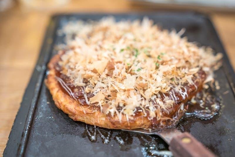 okonomiyaki; met de hand gemaakte stijl van het tranditional de Japanse voedsel en besnoeiing op een ijzerplaat klaar om bij een  royalty-vrije stock afbeeldingen