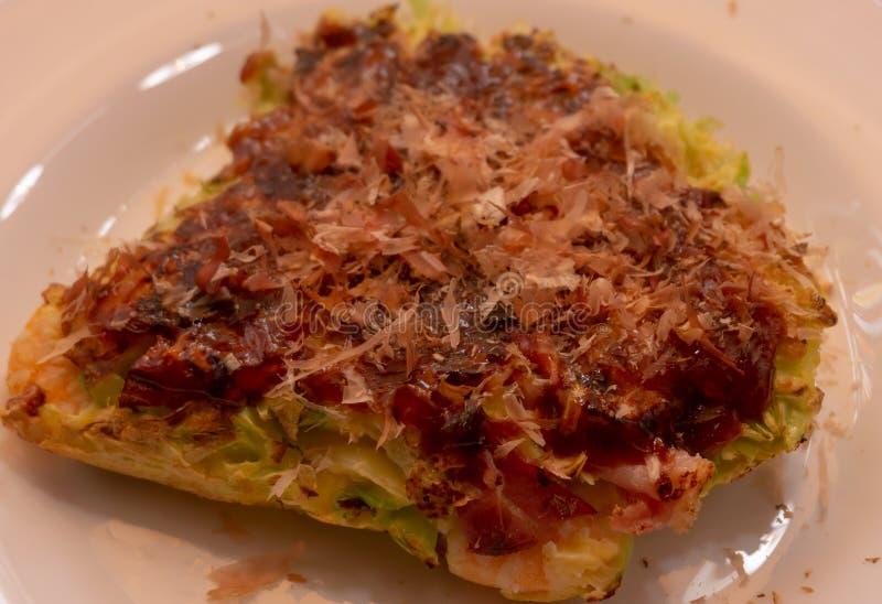Okonomiyaki - panqueca japonesa com bacon e couve, um molho picante e polvilhado com o bonito fotografia de stock royalty free