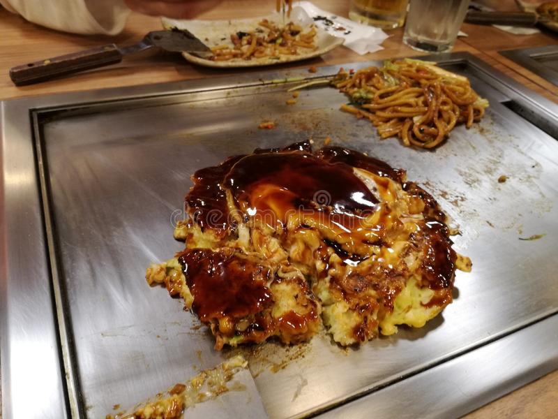 Okonomiyaki: a thick omelette cooked on the plate stock image
