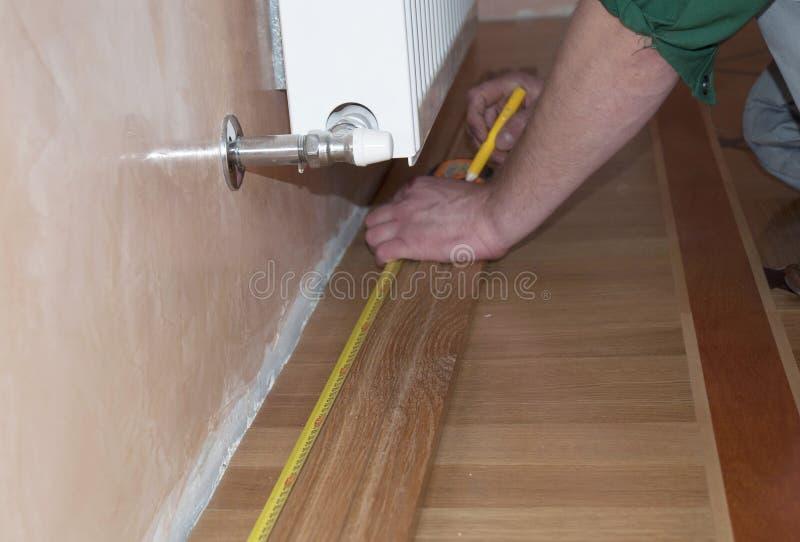 Okrążanie architraw & deska Repairman ` s wręcza Instalować okrążanie deskę Dębowa Drewniana podłoga zdjęcia royalty free