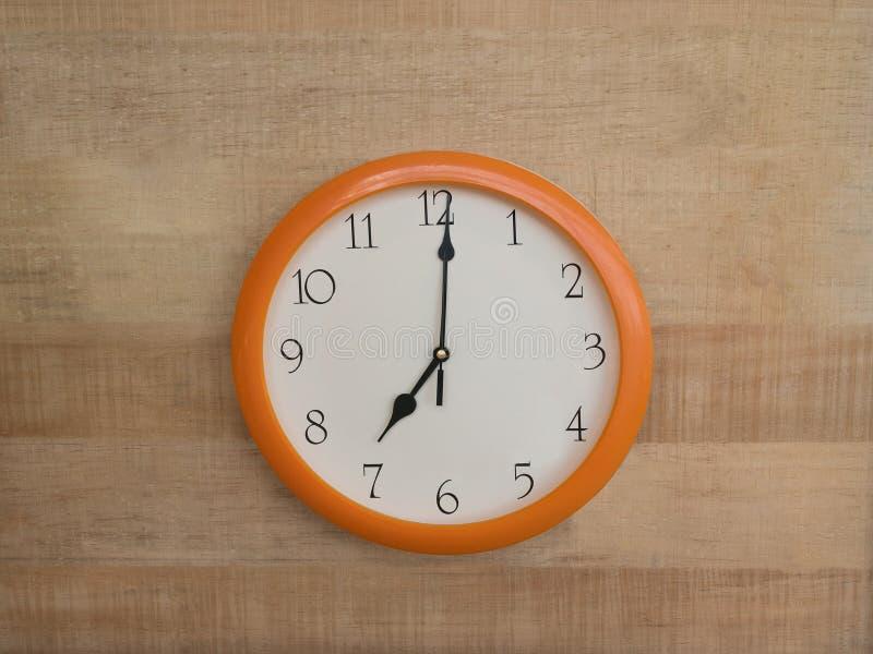 Okrągły zegar ścienny na drewnianym tle. Godzina siódma obrazy stock