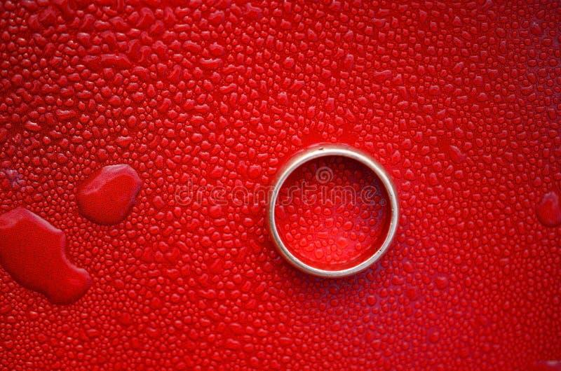 Okrąg kształtuje z wodą opuszczającą na czerwonym stalowym tle zdjęcia royalty free