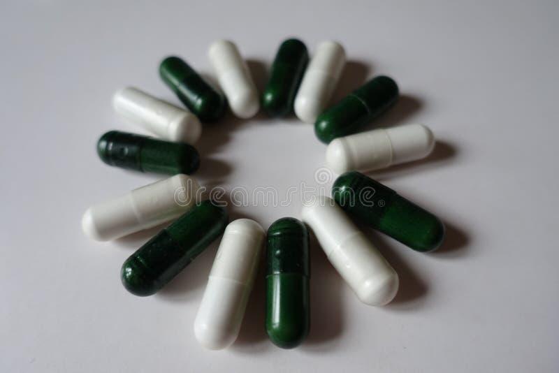 Okrąg zieleni multivitamins i białe magnez kapsuły obrazy royalty free
