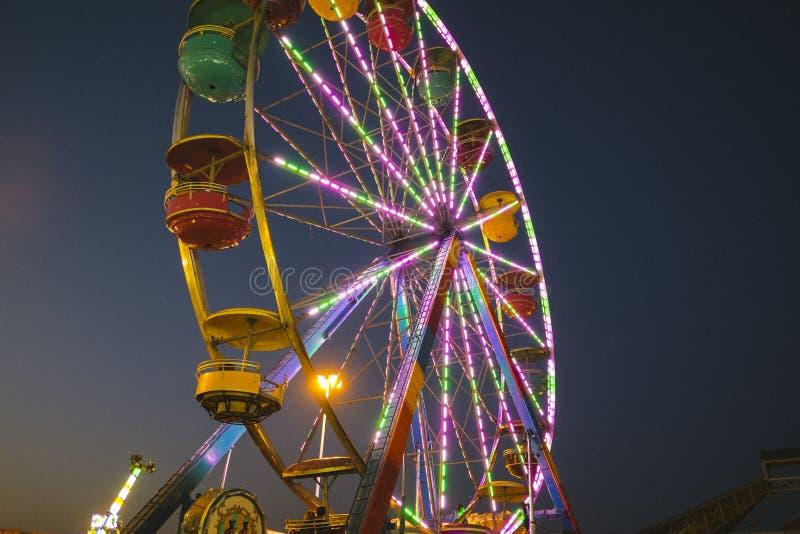 Okręgu administracyjnego jarmark przy nocy Ferris kołem na Midway obraz royalty free
