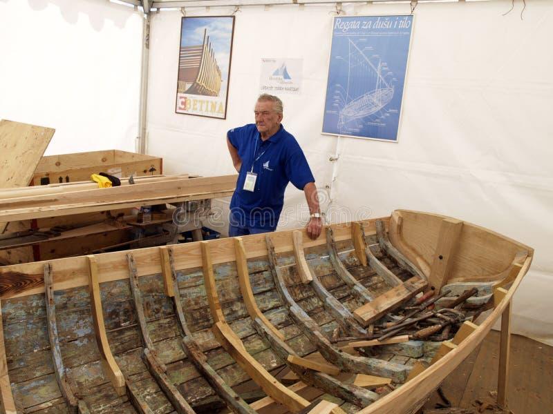 Okrętowiec pozuje opierać na starej drewnianej łodzi zdjęcie stock