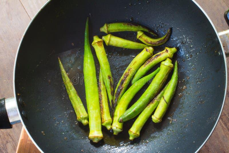 Okra in de pan wordt gekookt die stock foto