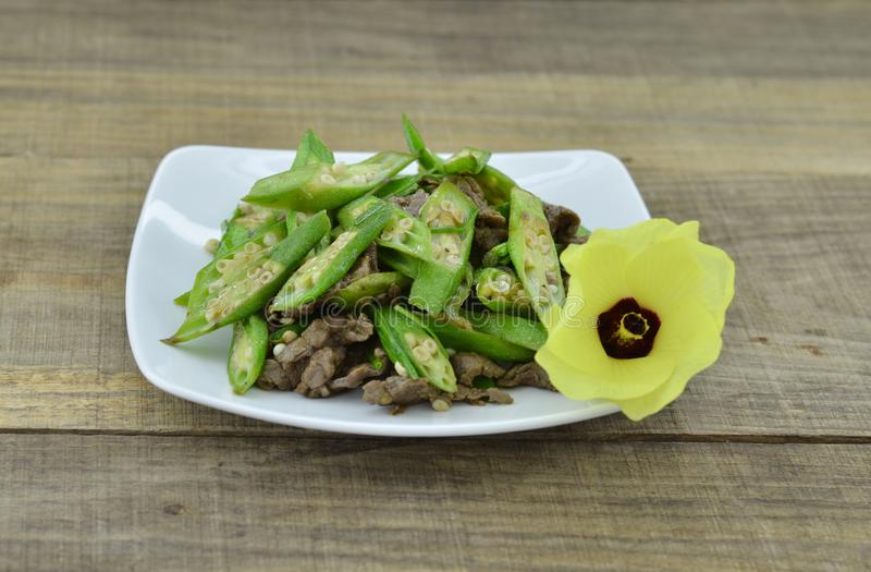 Okra fry with beef in white plate on wooden table stock photos