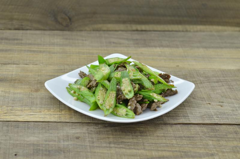 Okra fry with beef in white plate on wooden table royalty free stock image