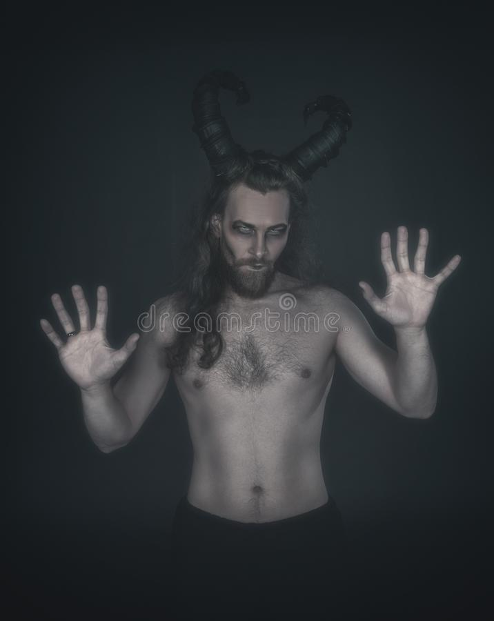 Okropny demon z rogami na zmroku obrazy stock