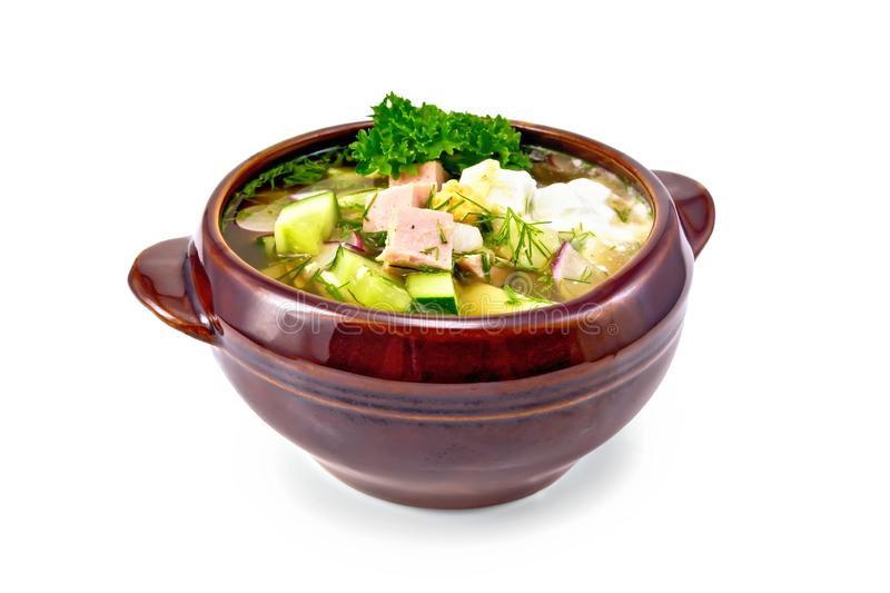 Okroshka in bowl. Cold soup okroshka from sausage, potatoes, eggs, radish, cucumber, greens and kvass drink in a clay bowl with a light shade on white background stock images