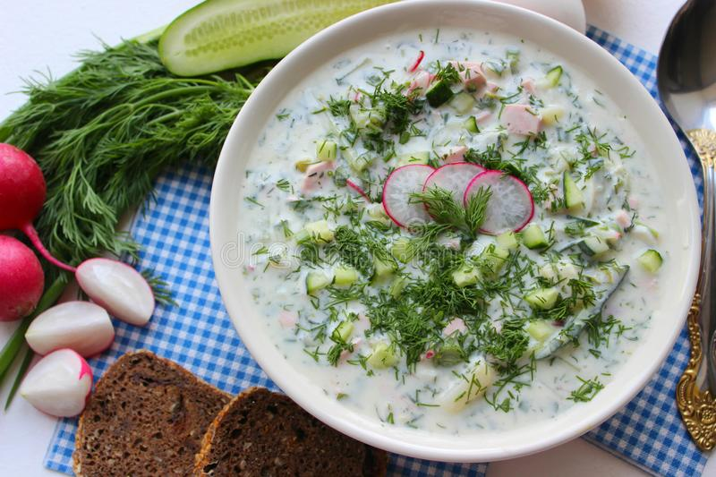 Okroshka. Cold soup. Okroshka is a traditional Russian summer cold soup in a ceramic bowl. Ingredients potatoes, radishes, cucumbers, dill, eggs, kefir yogurt royalty free stock photo