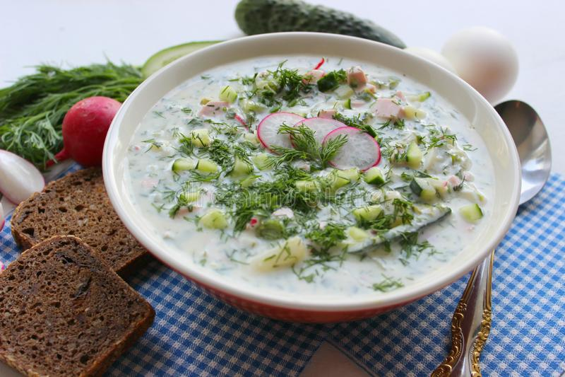 Okroshka. Cold soup. Okroshka is a traditional Russian summer cold soup in a ceramic bowl. Ingredients potatoes, radishes, cucumbers, dill, eggs, kefir yogurt royalty free stock image