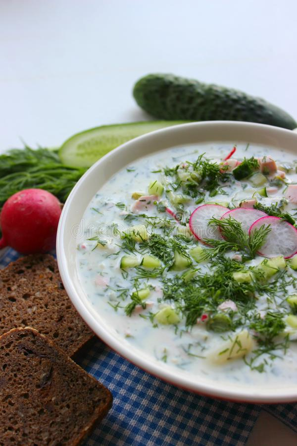 Okroshka. Cold soup. Okroshka is a traditional Russian summer cold soup in a ceramic bowl. Ingredients potatoes, radishes, cucumbers, dill, eggs, kefir yogurt royalty free stock photos
