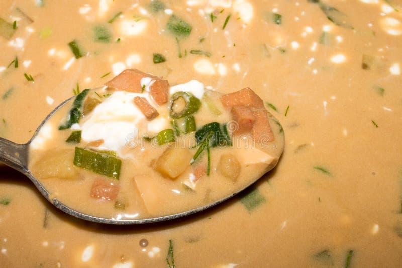 Okroshka on kvass. Background of okroshka on kvass with sausage and herbs stock photo