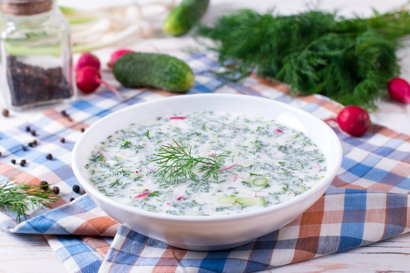 Okroshka Sopa fría ligera del yogur del verano con el pepino, el rábano, los huevos y el eneldo en una tabla foto de archivo