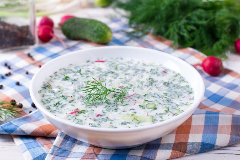 Okroshka. Summer light cold yogurt soup with cucumber, radish, eggs and dill on a table. stock photo