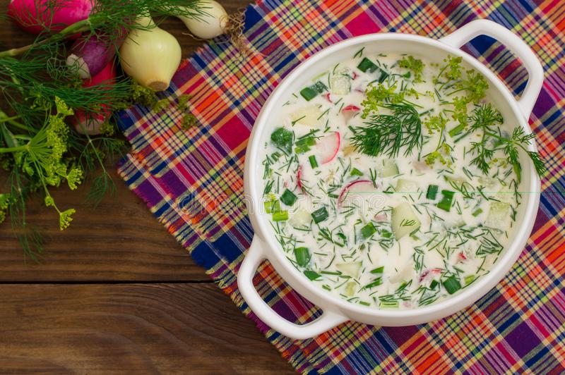 Okroshka. Summer light cold yogurt soup with cucumber, radish, eggs and dill on a wooden table. Wooden background. Close. Okroshka. Summer light cold yogurt soup stock photography
