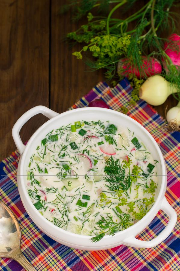 Okroshka. Summer light cold yogurt soup with cucumber, radish, eggs and dill on a wooden table. Wooden background. Close. Okroshka. Summer light cold yogurt soup stock photos