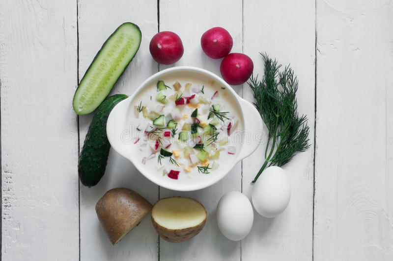 Okroshka. Traditional russian Summer yoghurt cold soup with vegetables on the white wooden table stock photo