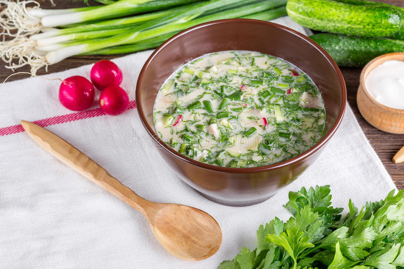 Okroshka. On a wooden table, cold soup, Russian national cuisine, spring onions, summer food stock photo