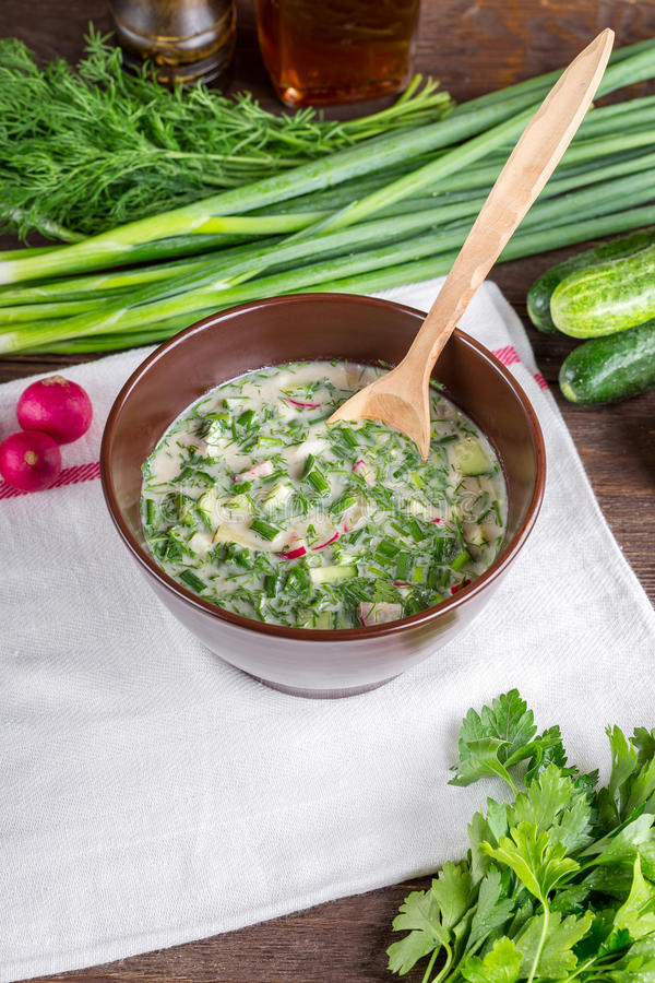 Okroshka. On a wooden table, cold soup, Russian national cuisine, spring onions, summer food royalty free stock image