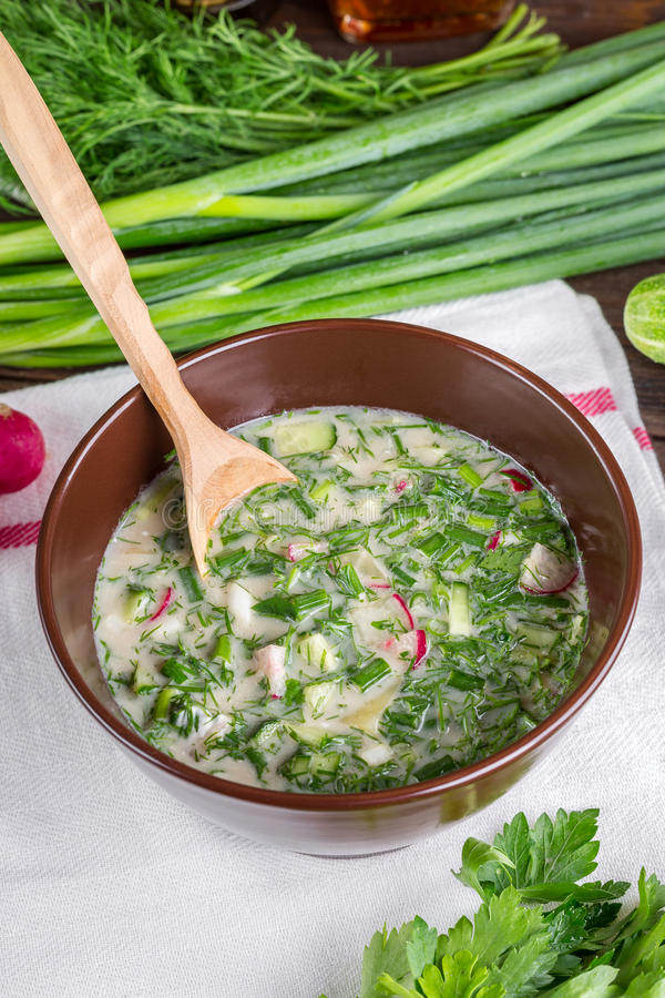 Okroshka. On a wooden table, cold soup, Russian national cuisine, spring onions, summer food stock photography