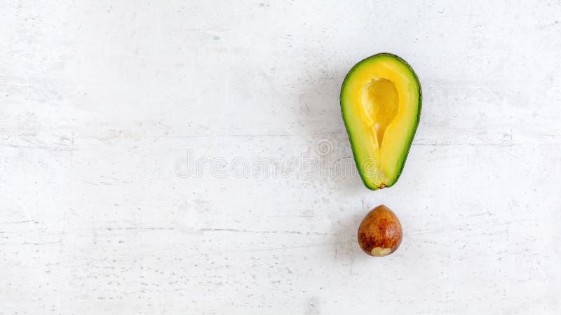 Okrzyk ocena robić avocado ziarno i połówka, na białej desce, fotografia z góry Szeroki sztandar z przestrzenią dla teksta na lew zdjęcia royalty free