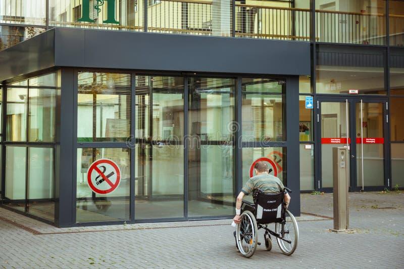 20 oktober, 2018 Duitsland Kliniek Helios Krefeld Een mens is gehandicapt op een rolstoel met zijn rug dichtbij de ingang aan royalty-vrije stock foto's