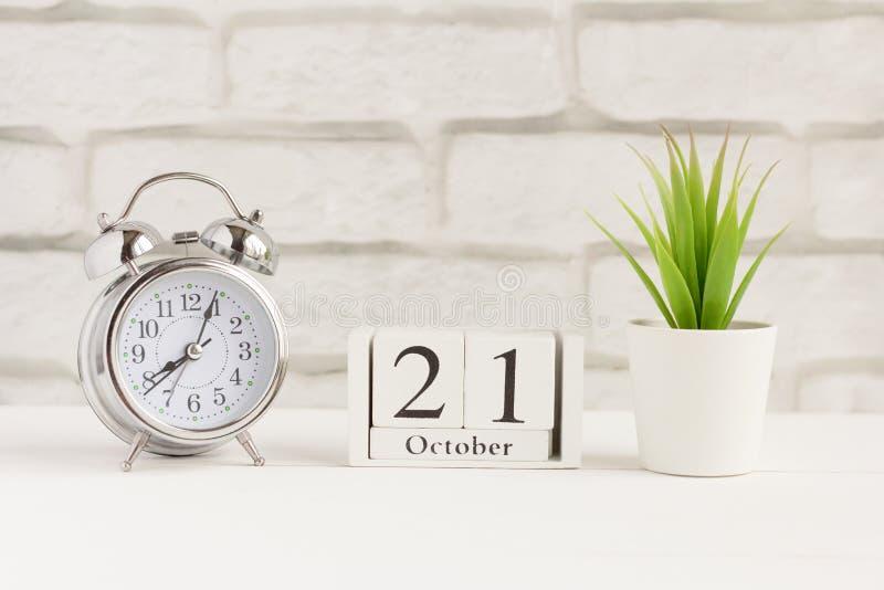 21 oktober op een houten kalender naast de wekker, de datum van de herfstmaand royalty-vrije stock afbeelding