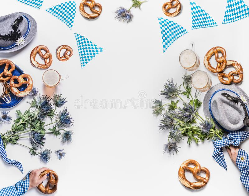 Oktoberfest background. Mugs of beer, Bavarian hats with feather, pretzel, woman hands in traditional blue blouse and alpin stock image
