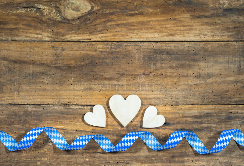 Oktoberfest Background. Rustic wooden hearts border with blue and white checkered ribbon at bavarian style. Background for Oktoberfest stock photography