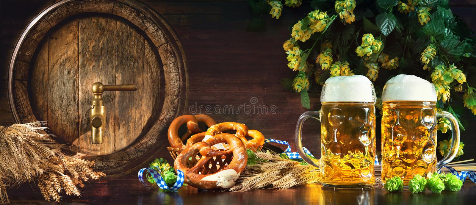 Oktoberfest beer barrel and beer glasses with soft pretzels, wheat and hop stock photos