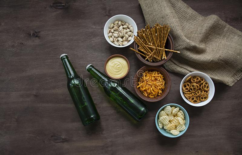 Oktoberfest beer with pretzels and various kinds of savory snacks. Beer snacks. Wood background. View from above. Place for text royalty free stock image