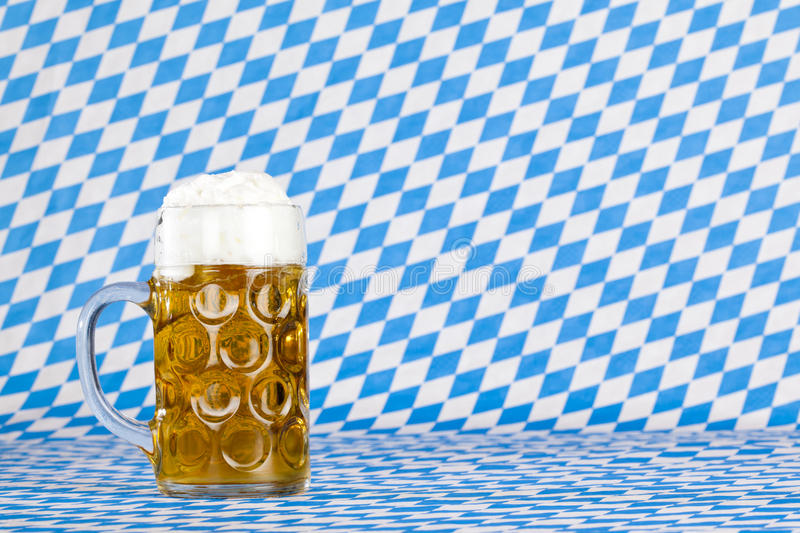 Oktoberfest beer stein and Bavarian flag. In background stock photography