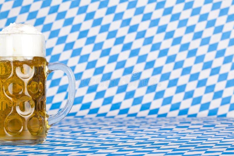 Oktoberfest beer stein with bavarian flag. Oktoberfest beer stein and Bavarian flag in background stock images
