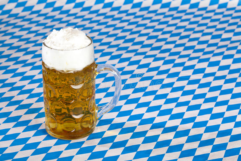 Oktoberfest beer stein on Bavarian flag. Oktoberfest beer stein and Bavarian flag in background stock photos